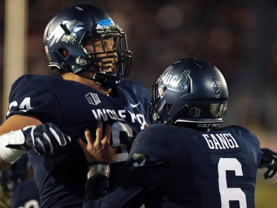 Wolf Pack center Sean Krepsz celebrates with quarterback Ty Gangi after a touchdown against Hawaii this season.