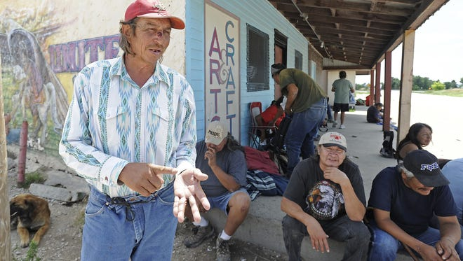 Stanley Flying Hawk, left, hangs out Aug. 1, 2013, in Whiteclay, Neb. Tribal members cross the state and reservation border to Whiteclay to buy alcohol.