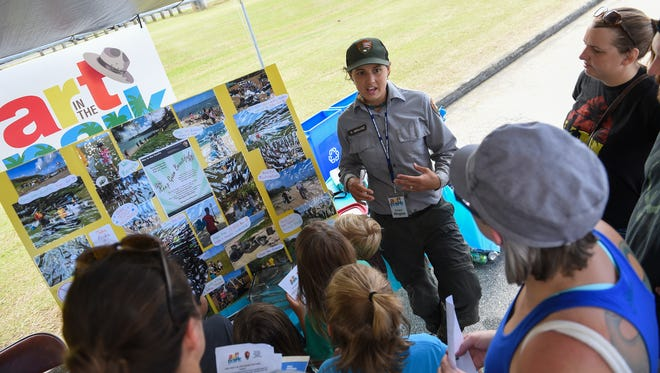 "Park Ranger Megan Hernandez informs attendees about island beautification during the War in the Pacific National Historical Park's ""Art in the Park"" event in Asan on Jan. 21, 2017."