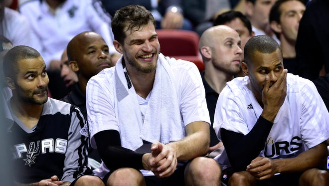 Spurs guard Tony Parker (left), center Tiago Splitter (center) and guard Patty Mills (right) like what they are seeing in the fourth quarter of their Game 4 rout of the Heat Thursday night in the NBA Finals.
