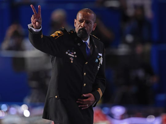 Sheriff David Clarke flashes the V-sign on stage during the evening session of the Republican National Convention at the Quicken Loans arena in Cleveland, Ohio on July 18, 2016.