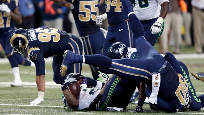 Seattle Seahawks running back Marshawn Lynch, bottom, lands on his back after being stopped on fourth down as St. Louis Rams players celebrate on the final play in overtime of an NFL football game in St. Louis. Seattle Seahawks coach Pete Carroll brushed aside comments made by Marshawn Lynch's mother Delisa Lynch in a Facebook post criticizing the organization and calling for offensive coordinator Darrell Bevell to be fired.  Her comments came after her son was stopped on a fourth-and-1 run play in overtime in the Seahawks' 34-31 loss in St. Louis on Sunday, Sept. 13, 2015..