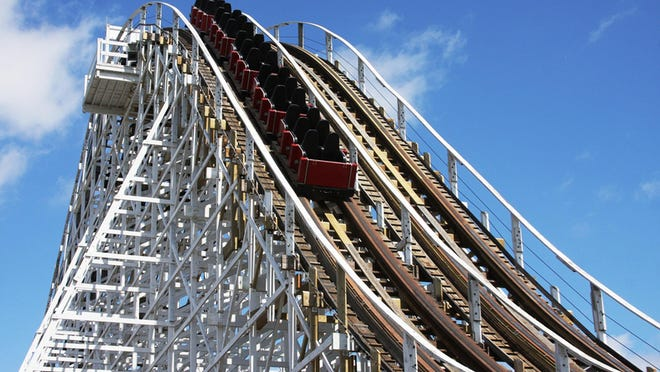 A train plummets down the first drop of the Racer roller coaster at Kings Island in this 2013 file photo.