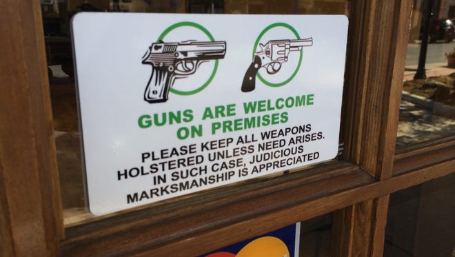 A sign on the front door of Shooters Grill in Rifle, Colo., welcomes patrons to carry handguns inside. All of the restaurant's waitresses carry handguns while working.  [Via MerlinFTP Drop]