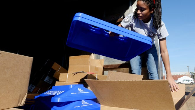 Shatavia Fullwood prepares for the Independence by sorting through the tops of the 40 recycling bins that Shreveport Green received because of a grant.