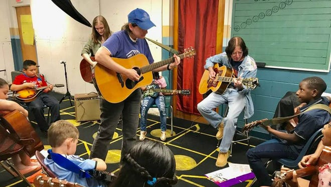 Al Bouler helps during a recent MAMA music education workshop at the Chisholm Boys & Girls Club.