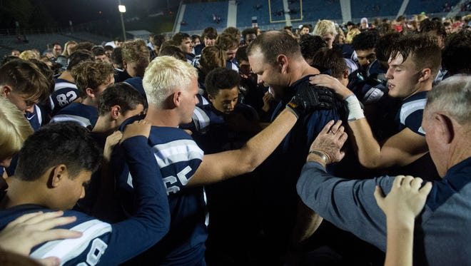 Reitz Head Coach Andy Hape prays with his team after their 49-46 win over the Mater Dei Wildcats at the Reitz Bowl in Evansville, Ind., on Saturday, Oct. 14, 2017.