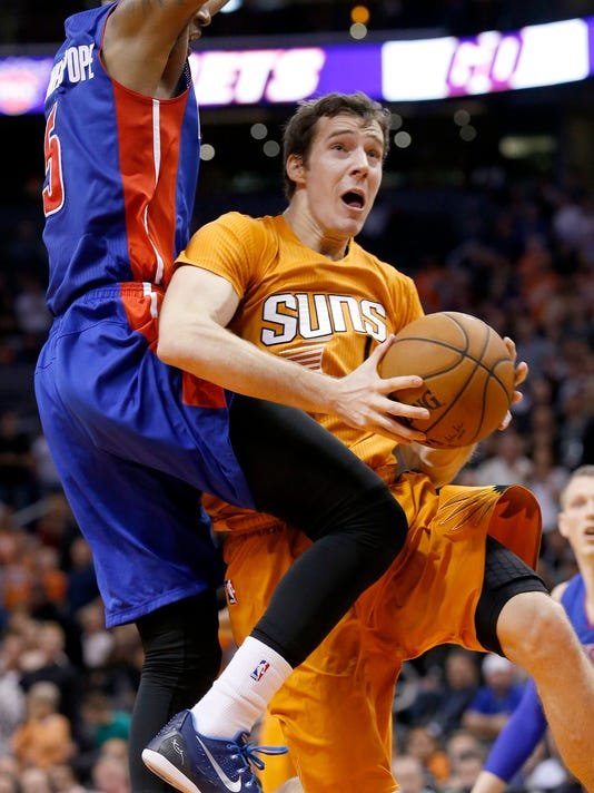 Phoenix Suns' Goran Dragic, right, of Slovenia, drives past Detroit Pistons' Kentavious Caldwell-Pope, left, during the second half of an NBA basketball game Friday, Dec. 12, 2014, in Phoenix.  The Pistons defeated the Suns 105-103. (AP Photo/Ross D. Franklin)