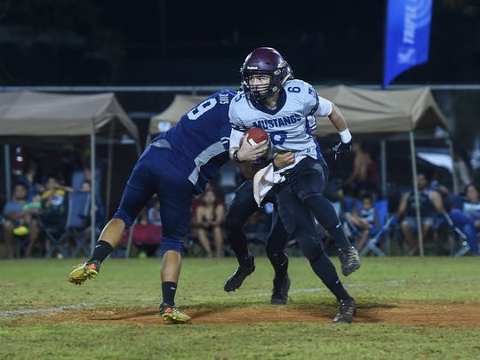 Father Duenas all-star Daniel Phillips (6) spins by an opponent during the Triple J Ford High School Football All-Star game at Hal's Angels Field in Dededo on Nov. 11, 2017.