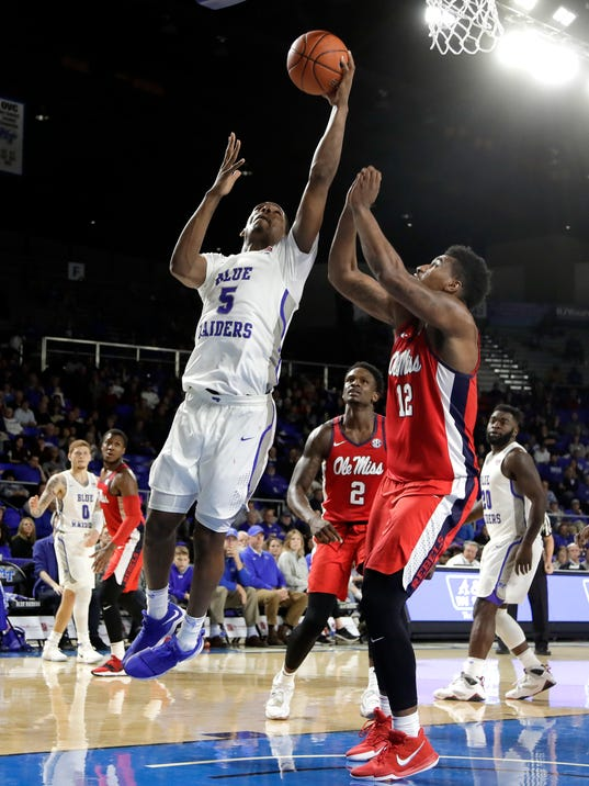 FILE - In this Dec. 9, 2017, file photo, Middle Tennessee forward Nick King (5) scores against Mississippi forward Bruce Stevens (12) during the second half of an NCAA college basketball game, in Murfreesboro, Tenn. Middle Tennessee has relied heavily on transfers during its gradual emergence as one of the nation's top mid-major powers. That pattern is continuing this year, as former Memphis and Alabama forward Nick King leads Middle Tennessee in scoring and rebounding while helping the 24th-ranked Blue Raiders reach the Top 25 for the first time in school history. (AP Photo/Mark Humphrey)