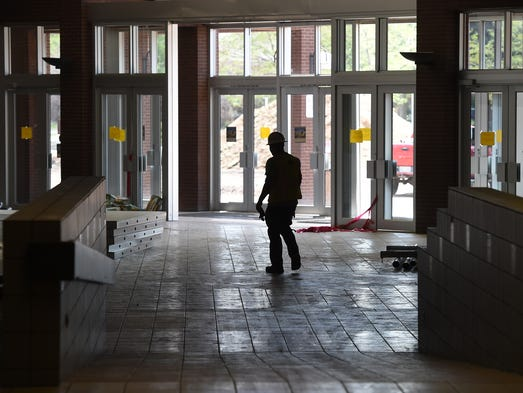 A worker walks by the old south entrance at the Foothills Mall redevelopment Thursday July 17, 2014.