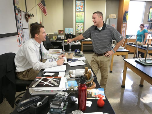 Scott Moore, Greensburg High School baseball coach,right, talks to his former player and now substitute teacher Alex Meyer,left, before class  starts at Greensburg High School.