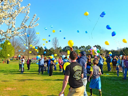 Blue and yellow balloons are released into the sky