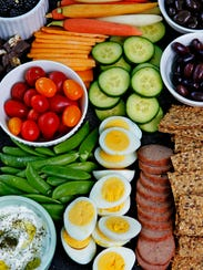 A snack board featuring fresh vegetables, crackers,
