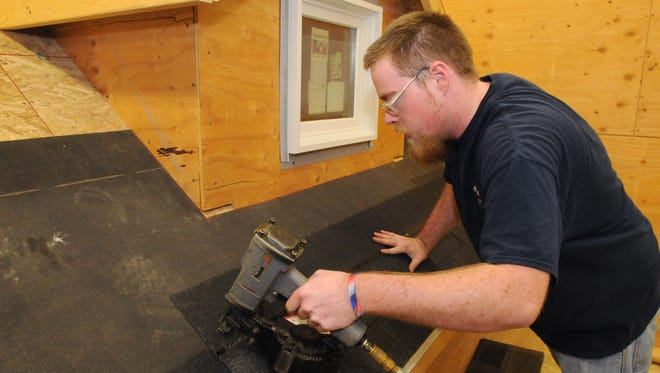 Kevin Atkinson, a Fox Valley Technical College construction intern is doing roofing on a mock building that is inside the construction program at FVTC so that students can work on the building in a classroom setting.