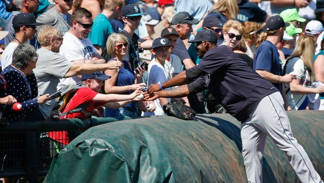 Seattle Mariners' Jabari Blash signs autographs prior to the start of a spring training baseball game against the Texas Rangers Friday, March 20, 2015, in Surprise, Ariz.