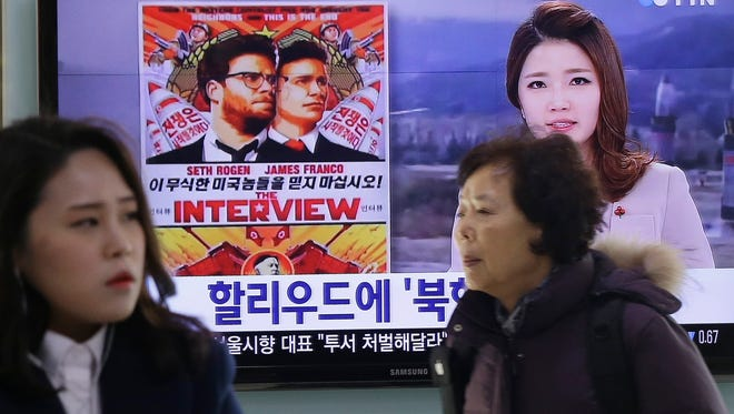 """In this Monday file photo, people walk past a TV screen showing a poster of Sony Picture's """"The Interview"""" in a news report,  at the Seoul Railway Station in Seoul, South Korea."""