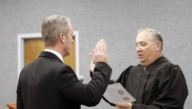 Judge Carlton Gray administers the oath of office to Victor Snover Monday at Aztec City Hall. Snover was appointed mayor during the commission meeting.