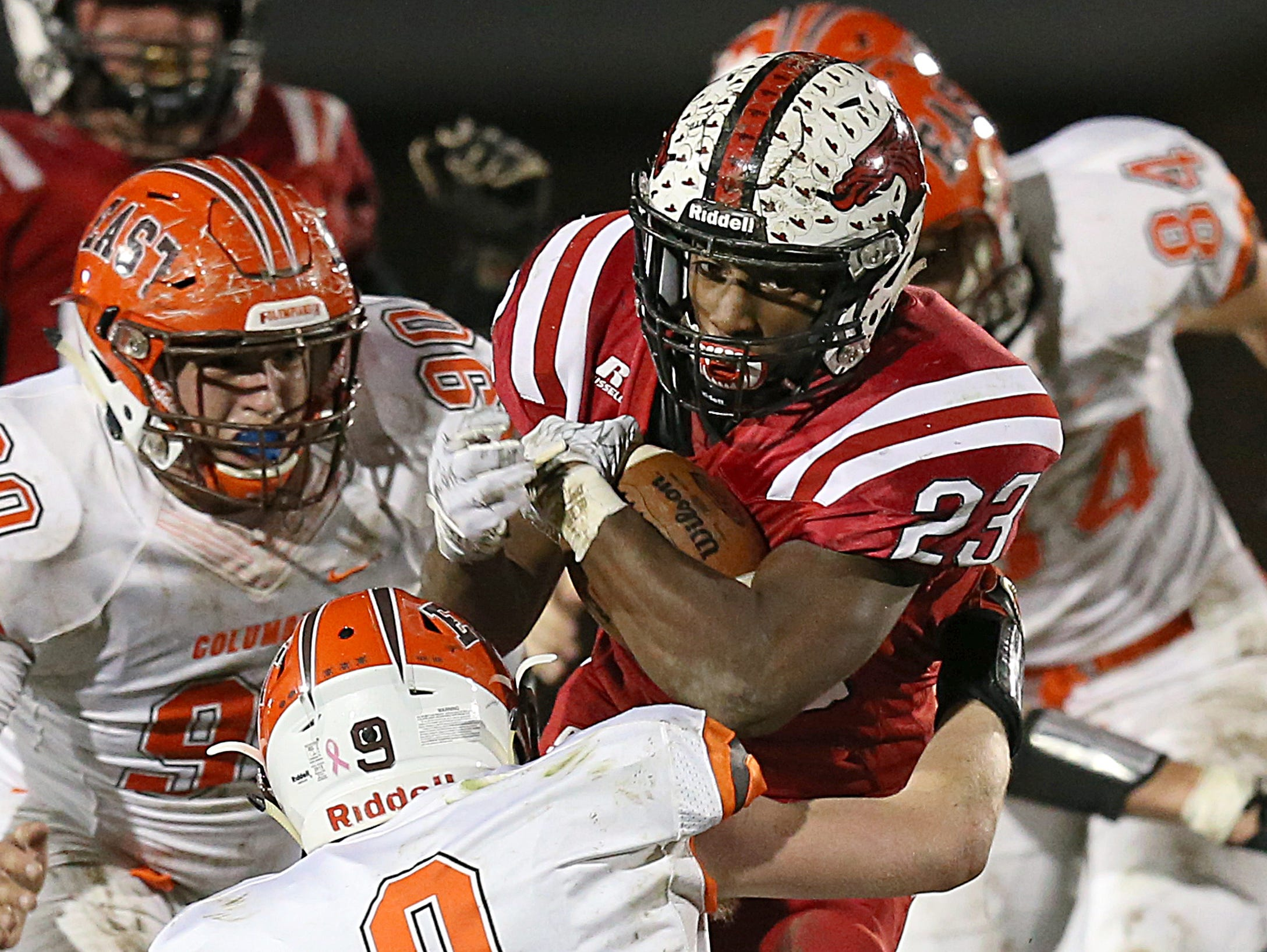 New Palestine Dragons DuRon Ford (23) carries the ball through a cluster of Columbus East defenders during first half action between New Palestine and Columbus East in New Palestine, Ind., Friday, October 21, 2016.Columbus East led, 20-7 at the end of the first half.