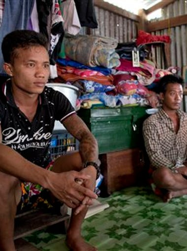 In this July 1, 2015, photo, former Burmese slave fishermen Kaung Htet Wai, left, and Lin Lin sit in a small, wooden shack in Yangon, Myanmar. They recently returned home after being forced to work off the coast of Papua New Guinea following a crackdown on illegal fishing in neighboring Indonesia. They say hundreds of other men remain unaccounted for and are believed to be fishing in those same, dangerous waters.
