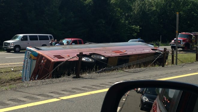 A Canadian tour bus carrying 54 people from Quebec City to New York City rests on its side after rolling over on the Northway in the Adirondacks in Essex County, N.Y., Friday, July 18, 2014. One person was killed and several others injured. (AP Photo/Adirondack Daily Enterprise, Catherine Moore)