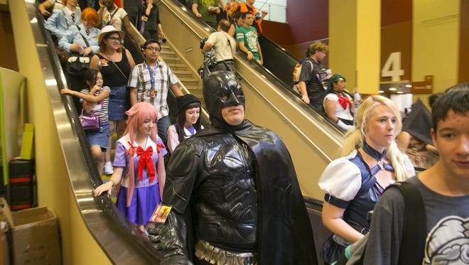 People take the escalators down to the exhibit hall at Phoenix Comicon at the Phoenix Convention Center on Friday, June 3, 2016.