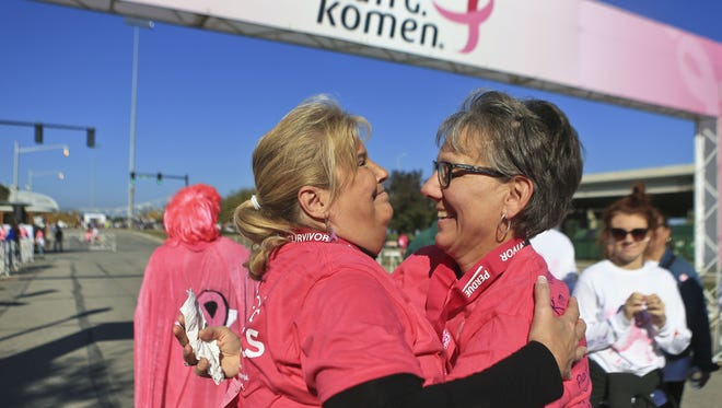 Kim Lucas, left, hugs sister-in-law Amanda Lucas after the two crossed the finish line during the 20th anniversary Komen Race for the Cure. (file art)