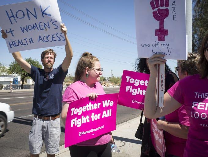 Chris Hanlon, left, and April Miller, right, protest