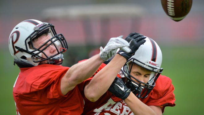 Pierz senior running back Derick Hall, left, disrupts a pass intended for teammate Lukas Otte during defensive practice drills Tuesday, Oct. 11, at Pierz Healy High School.