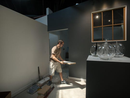 """Artist Mike Krupiarz works on an installation for the """"Glassville"""" exhibition in the second floor space of the Center for Craft, Creativity & Designs on Wednesday."""