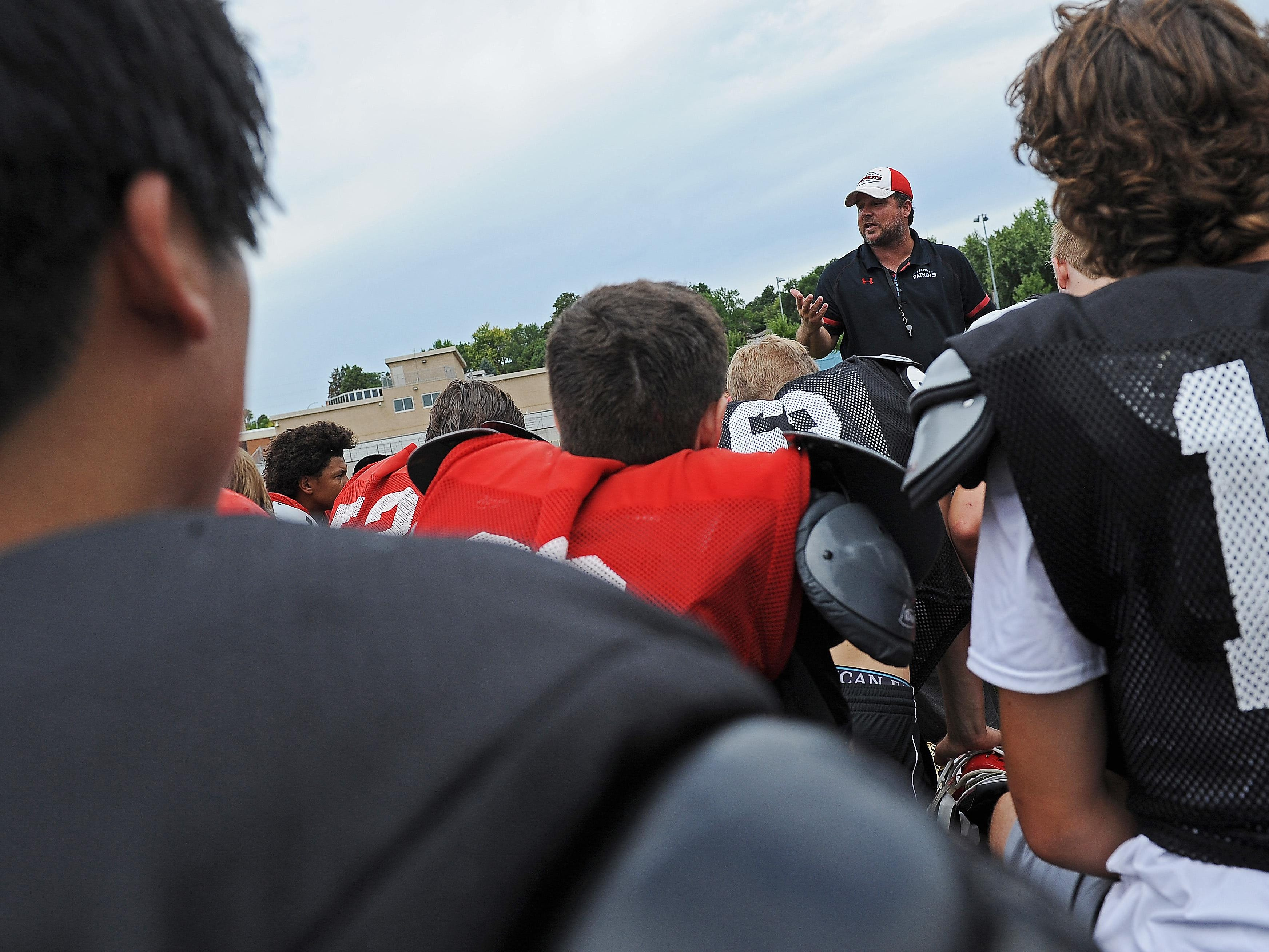 Lincoln High School football coach Aaron Beavers speaks to his team during a Lincoln High School football practice Thursday, Aug. 11, 2016, at Lincoln High School in Sioux Falls.