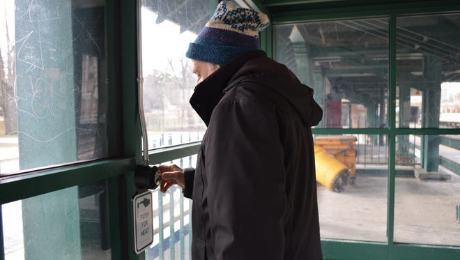 A Metro-North rider at the Woodlawn station in the Bronx uses one of the railroad's new push-button heaters, which have been installed at station shelters on the Harlem and Hudson lines. They will be added along the New Haven line in coming months. The railroad says they save energy and money.