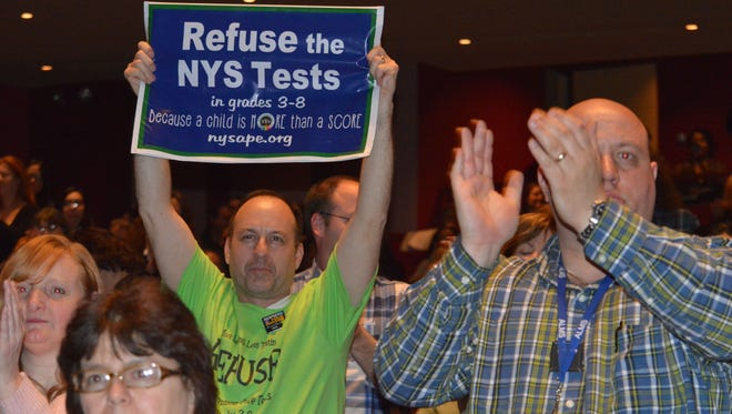 A Brewster parent held up a sign at Purchase College on Thursday, urging others to opt out of New York's standardized tests for grades 3 to 8.