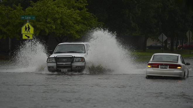 A stalled vehicle, at right, sits in water on Oneida Street in Green Bay after heavy rain flooded area streets on Monday.