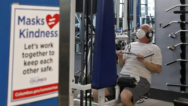"A sign at Powerhouse Gym Downtown urges patrons to wear a mask, and Michael Knowlton of Commercial Point complies during a recent workout. However, a patron at another area gym said ""probably 90%"" walked around the facility without their mask on."