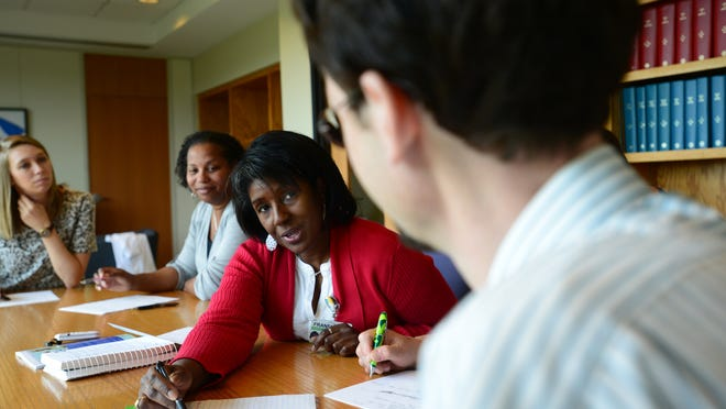 Franella Obi, center, works with Greenville Health System Writing Group participant Dan Powell, right, on a Haiku.