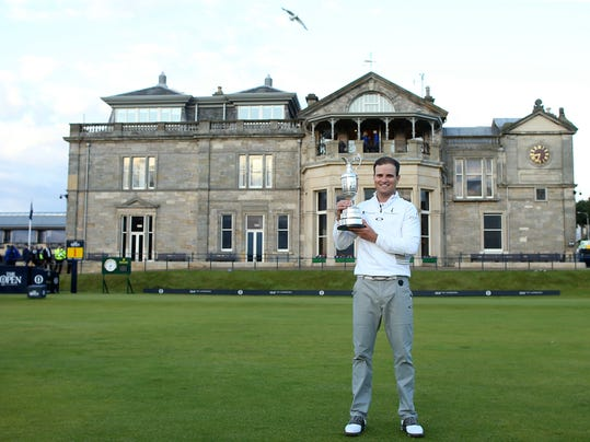 "FILE - A Monday, July 20, 2015 file photo of United States' Zach Johnson posing with the claret jug trophy after winning a playoff after the final round at the British Open Golf Championship at the Old Course, St. Andrews, Scotland. The British Open is returning to the home of golf in 2021. The Old Course will host the 150th anniversary of the world's oldest major to mark ""a true celebration of golf's original championship and its historic ties to St Andrews,"" the R&A said Monday, Feb. 12, 2018. (AP Photo/Peter Morrison, File)"
