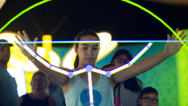 Penelope Vela, 13, of Paradise Valley, plays with an interactive exhibit at A Mirror Maze: Numbers in Nature in the Arizona Science Center in Phoenix on July 5, 2018.