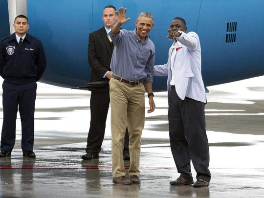President Barack Obama waves to Sheritta Johnson (not pictured), wife of St. Lucie County commissioner, Kim Johnson (right), before departing on Air Force One Sunday at the Treasure Coast International Airport and Business Park in St. Lucie County. Obama was visiting the Treasure Coast to play golf at Palm City's Floridian National Golf Club over the weekend. To see more photos, go to TCPalm.com (MOLLY BARTELS/TREASURE COAST NEWSPAPERS) CQ: Kim and Sheritta Johnson Taken: Sunday, June 5, 2016