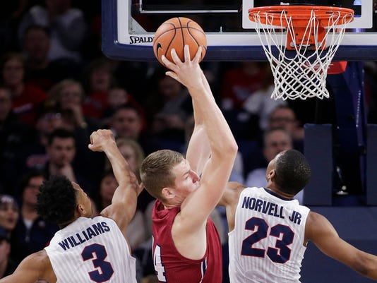 Loyola Marymount center Mattias Markusson, center, grabs a rebound between Gonzaga forward Johnathan Williams (3) and guard Zach Norvell Jr. (23) during the first half of an NCAA college basketball game in Spokane, Wash., Thursday, Feb. 15, 2018. (AP Photo/Young Kwak)