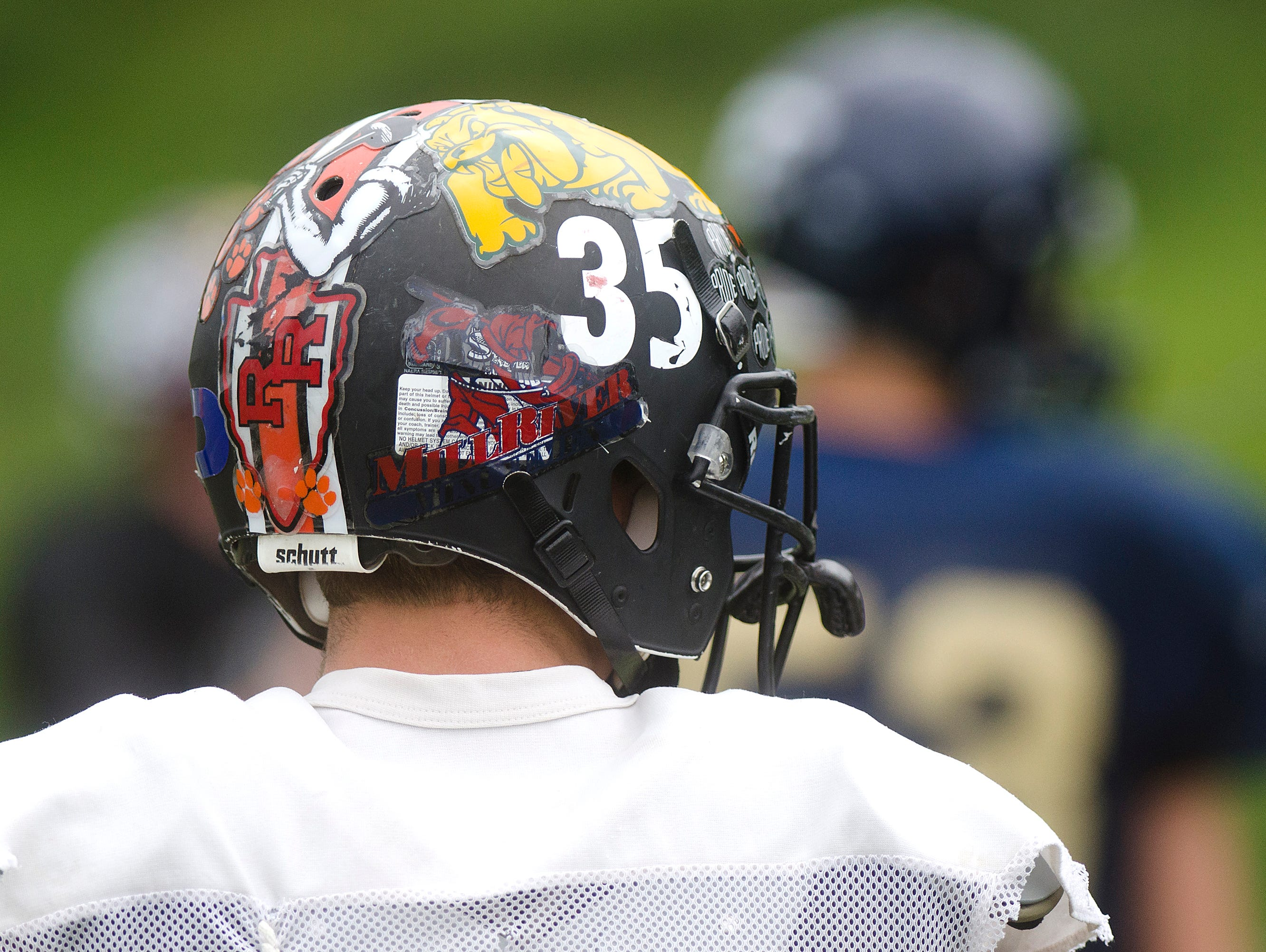 A variety of team decals adorn the helmet of Middlebury running back Jakob Trautwein during practice for the 61st Shrine Maple Sugar Bowl at Castleton State College on Monday.
