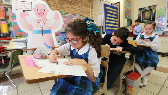 St. Raphael second-graders Aryssa Perez, from left, Raul Solis and Sofia Bernal work on assignments Thursday in teacher Katherine Conde's classroom. Flat Francis, a cardboard cartoonish figure of Pope Francis, accompanies them.