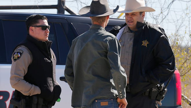 In this Saturday, Feb. 6, 2016 photo, Uvalde County Sheriffs Deputies talk with an individual while guarding the intersection to a neighborhood several miles outside of Uvalde after a standoff resulted in multiple deaths. The incident started on Friday.