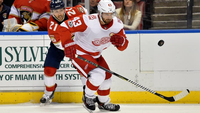 Red Wings left wing Darren Helm (43) and Panthers center Vincent Trocheck (21) chase a loose puck during the first period on Saturday, Oct. 28, 2017, in Sunrise, Fla.
