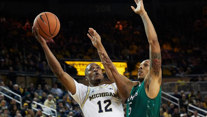 Michigan guard Muhammad-Ali Abdur-Rahkman (12) shoots against Jacksonville forward Damien Sears (5) in the first half on Saturday, Dec. 30, 2017, at Crisler Center.