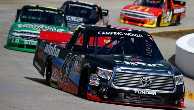 Ben Rhodes races ahead of Johnny Sauter and Kyle Busch during the NASCAR Camping World Truck Series Alpha Energy Solutions 250 at Martinsville Speedway on April 2, 2016 in Martinsville, Virginia.