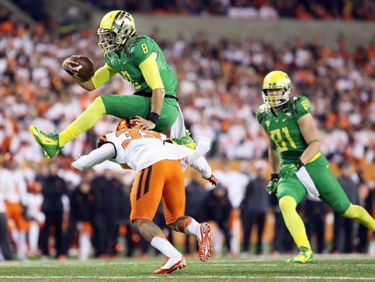 Marcus Mariota hurdles Justin Strong during the annual