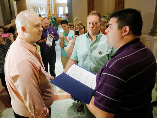 Matt Hicks, right,  of American Marriage Ministry, Indianapolis, officiates the wedding of Dan Peo, left, and Douglas Taylor Thursday, June 26, 2014, in the Tippecanoe County Courthouse. The couple were the first in line to obtain their marriage license from the Clerk's Office. Moments later, they took their marriage vows before a group of supporters.