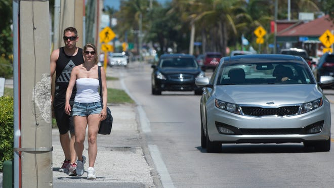 Visiting from Germany, Marcel Schar, left, and Sandra Budreli, walk on the side of Estero Boulevard in Fort Myers Beach. The construction of sidewalks on the side of Estero is scheduled to start soon.