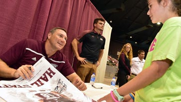 Mississippi State football coach Dan Mullen signs a poster for Brooke Barron, 10, Thursday during the annual MSU Summer Extravaganza at the Mississippi Coliseum.